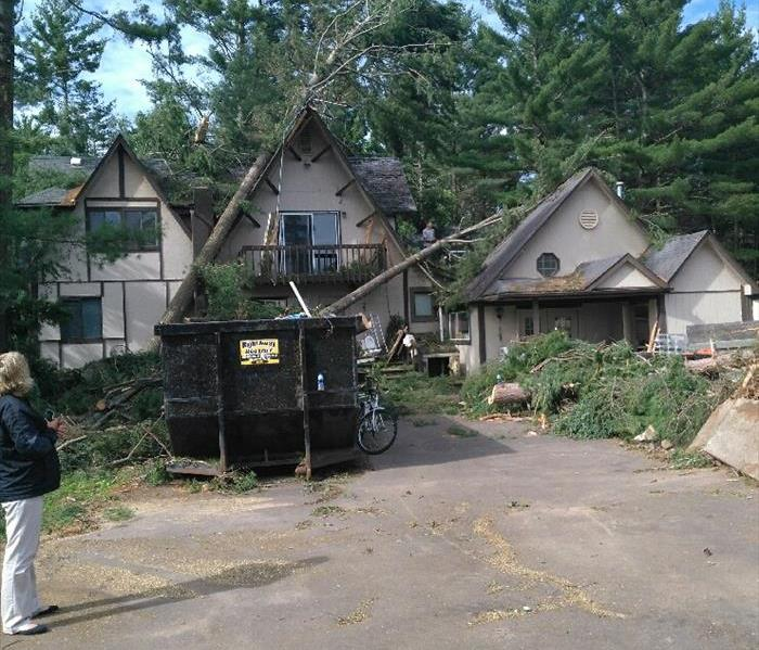 storm damaged home with trees down around the home