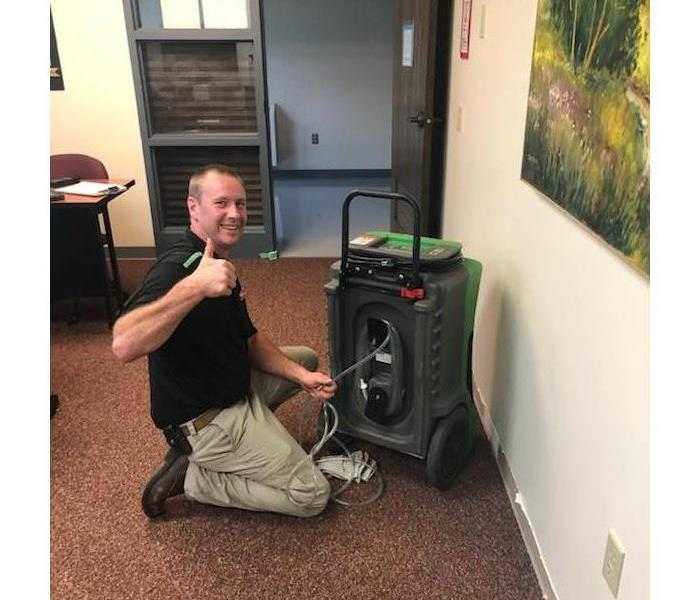 SERVPRO employee setting airmovers in a classroom