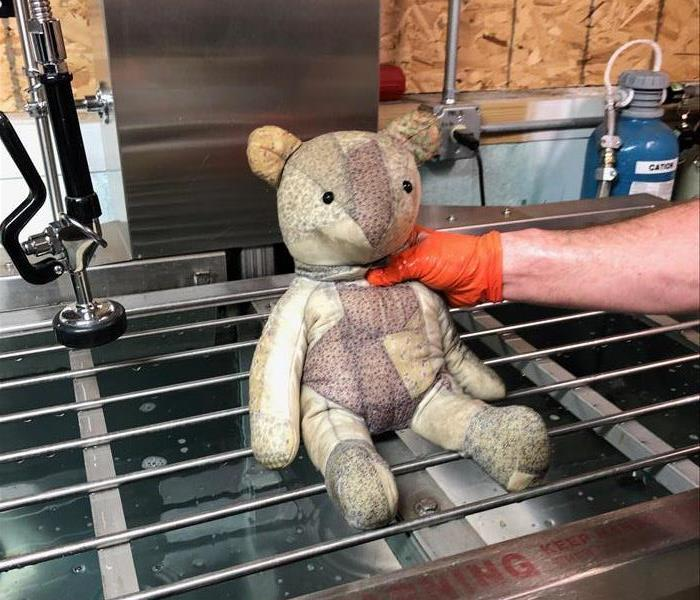 a teddy bear damaged by smoke and soot
